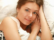 Portrait of beautiful woman, she lying on white bed