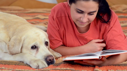 Young beautiful woman with Labrador on the bed. She is reading a