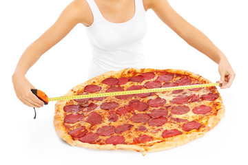 Woman measuring huge pizza