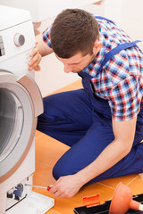Repairman fixing washing machine