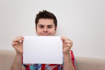 Junger Mann im Hemd auf Sofa mit Blatt
