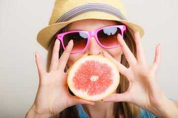 Summer. Girl tourist holding grapefruit citrus fruit