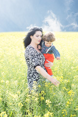 Mom showing to her son rapeseed flowers