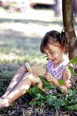 Adorable little girl in pigtails reading a book in the garden