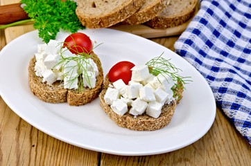 Bread with feta and tomatoes on plate on board