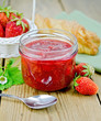 Jam of strawberry with bun and spoon on board