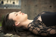 Pretty brunette young woman lying down on brick wall
