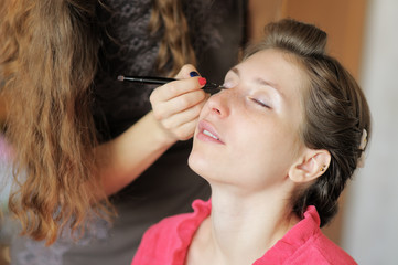 Young woman applying make-up by professional make-up artist