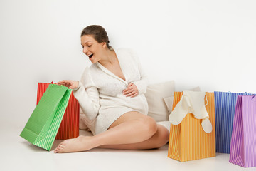 Smiling pregnant woman  opening shopping bag