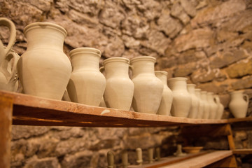 Pottery dishes on shelves in pottery workshop, editorial photo