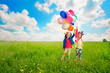 Children with balloons walking on spring field