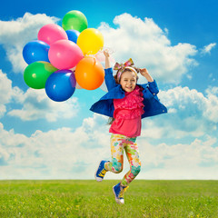 Little girl with balloons jumping on the field