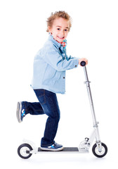 Cheerful boy going fast with scooter