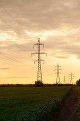 Silhouette of electricity pylons at sunset