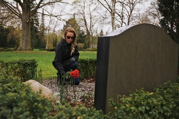 Young woman placing roses at a cemetery