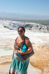 Aged woman on background of travertine pools in Pamukkale, Turke