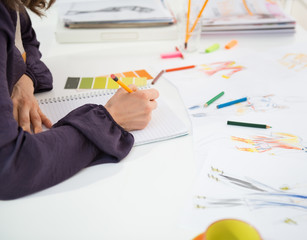 Closeup on fashion designer making sketches in office