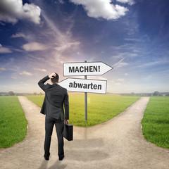 """Mann steht an zwei Wegen """"MACHEN - ABWARTEN"""""""
