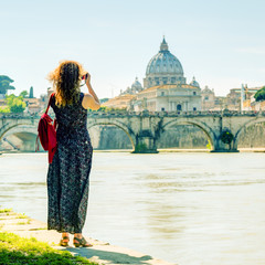Young woman photographs the Cathedral of St. Peter in Rome