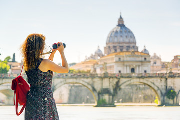 Young woman takes a picture of Cathedral of St. Peter in Rome