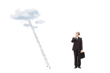 Businessman standing in front of a ladder