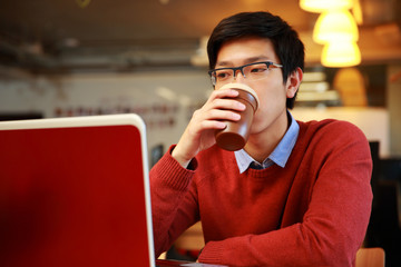 Young asian man working on laptop and drinking coffee