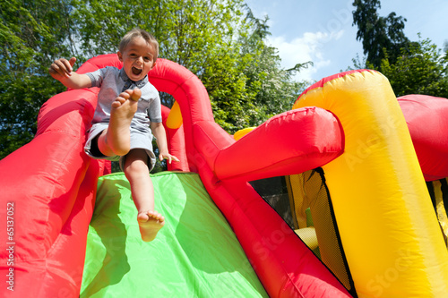 canvas print picture Child on inflatable bouncy castle slide