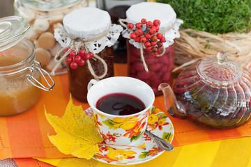 Чашка с чаем на фоне чайника и баночек