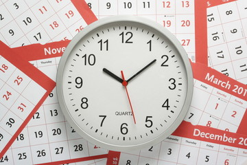 Office clock on a background of calendar pages