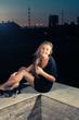 Blonde sitting on a parapet at night