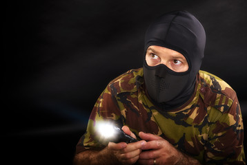 soldier on a black background with a flashlight in camouflage mi