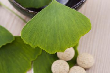 Ginkgo biloba leaves in mortar and pills