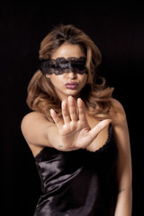 Blindfold woman making stop gesture