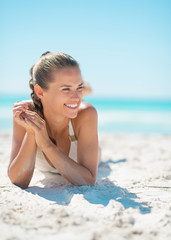Portrait of smiling young woman laying on beach