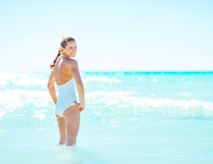 Happy young woman standing in sea