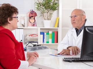 Älterer Arzt und Patientin im Gespräch