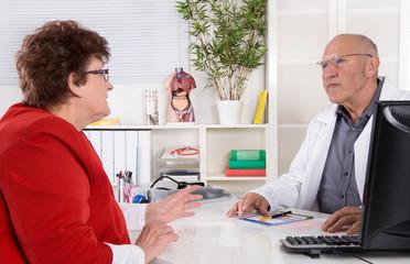 Besuch beim Arzt: Doktor und ältere Frau im Gespräch