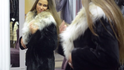 Young beautiful woman tries on a warm jacket in the mirror jacke