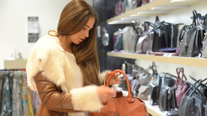 Young beautiful woman in a boutique. She chooses a bag.