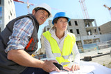 Engineers on building site checking plans