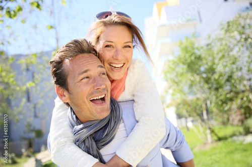 Man giving piggyback ride to woman in town - 65151070