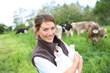 Smiling breeder woman holding bottles of milk