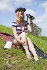 Woman sitting on grass holding binoculars