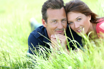 Loving couple laying in country field