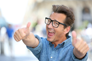 Cheerful guy with eyeglasses showing thumbs up