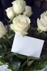 Ramo de rosas blancas y tarjeta en blanco