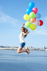 Happy young woman jumping with colorful balloons