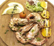 grilled shrimp with a salad on a wooden plate