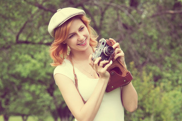 smiling girl in a cap with a camera in the garden