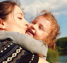 Mother kissing happy child outdoors summer background